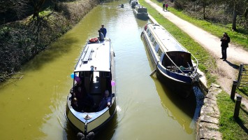 A holiday boat cruises down the Kennet and Avon Canal.